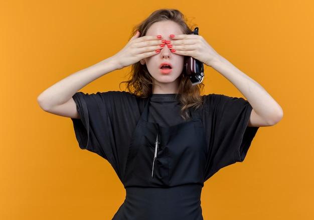 Pod wrażeniem młoda słowiańska fryzjerka ubrana w mundur trzymając maszynkę do strzyżenia włosów i zamykając oczy rękami na białym tle na pomarańczowym tle
