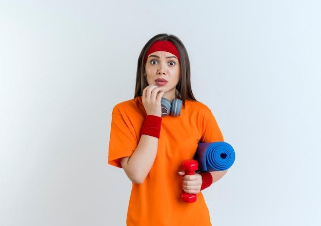 Pod wrażeniem młoda sportowa kobieta nosząca opaskę i opaski na nadgarstek oraz słuchawki na szyi trzymająca hantle z matą do jogi dotykająca brody, wyglądająca na odizolowaną