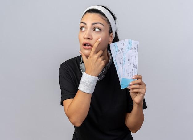 Pod wrażeniem młoda sportowa kobieta nosząca opaskę na głowę i opaski ze słuchawkami na szyi, trzymająca bilety lotnicze, trzymając rękę na brodzie, patrząc na bok na białym tle na białej ścianie