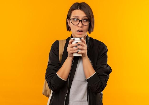 Pod wrażeniem młoda studentka w okularach iz powrotem trzyma plastikową filiżankę kawy patrząc na bok na białym tle na pomarańczowo