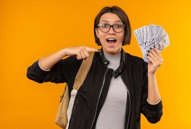 Pod wrażeniem młoda studentka w okularach iz powrotem trzymając i wskazując na pieniądze na pomarańczowym tle