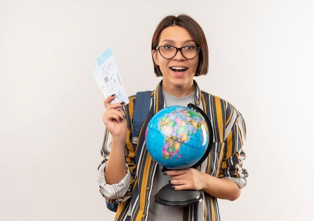 Pod wrażeniem młoda studentka w okularach iz powrotem worek trzymając bilety lotnicze i kula ziemska na białym tle