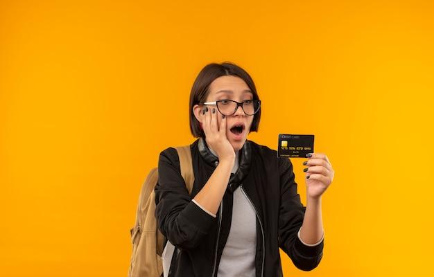 Pod wrażeniem młoda studentka w okularach iz powrotem worek trzymając i patrząc na kartę kredytową ręką na twarzy odizolowane na pomarańczowo