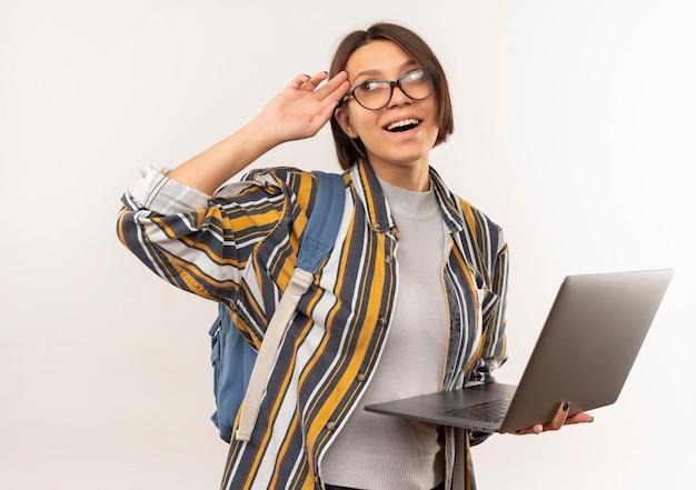 Pod wrażeniem młoda studentka w okularach iz powrotem worek trzymając laptopa patrząc na bok kładąc rękę na świątyni na białym tle
