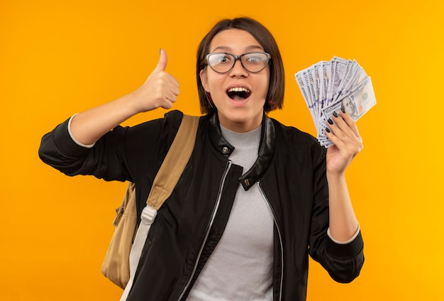 Pod wrażeniem młoda studentka w okularach iz powrotem worek trzymając pieniądze pokazując kciuk do góry na białym tle na pomarańczowo