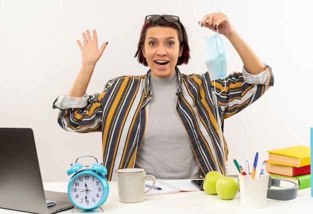 Pod wrażeniem młoda studentka w okularach na głowie siedzi przy biurku trzymając maskę i macha na białym tle