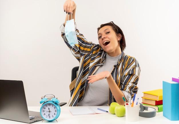 Pod wrażeniem młoda studentka w okularach na głowie siedzi przy biurku trzymając maskę i pokazując pustą rękę na białym tle