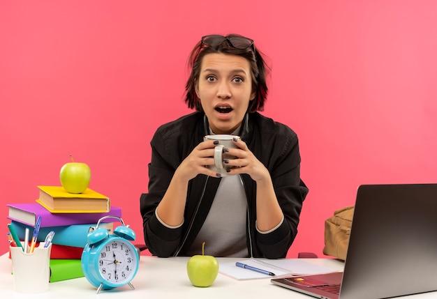 Pod wrażeniem młoda studentka w okularach na głowie trzyma filiżankę kawy siedzi przy biurku, odrabiania lekcji na różowym tle
