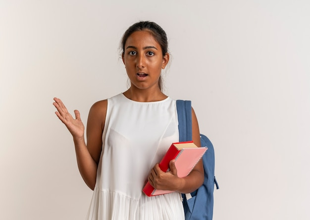 Pod wrażeniem młoda uczennica na sobie plecak, trzymając książkę z notatnikiem i pokazując ręką przy boku