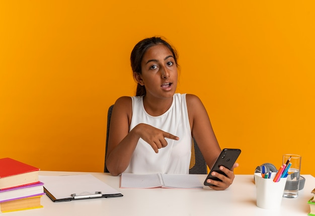 Pod wrażeniem młoda uczennica siedzi przy biurku z narzędziami szkolnymi i wskazuje na telefon