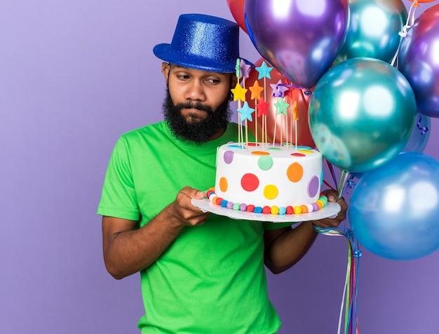 Pod wrażeniem młodego afroamerykańskiego faceta w imprezowym kapeluszu, trzymającego i patrzącego na balony z ciastem