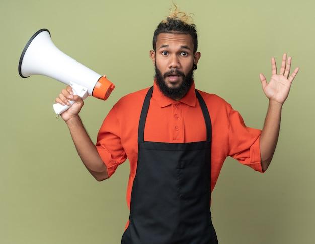 Pod wrażeniem młodego afroamerykańskiego fryzjera w mundurze trzymającym głośnik pokazujący pustą rękę