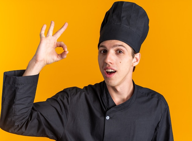 Pod wrażeniem młodego blond kucharza w mundurze szefa kuchni i czapce, patrząc na kamerę robi ok znak na pomarańczowej ścianie
