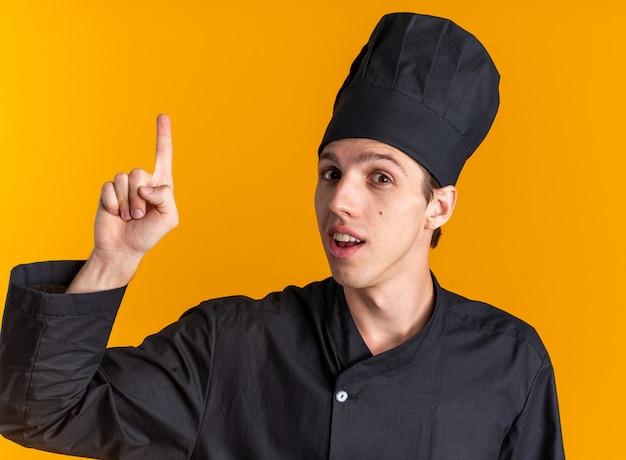 Pod wrażeniem młodego blond kucharza w mundurze szefa kuchni i czapce, patrząc na kamerę skierowaną w górę odizolowaną na pomarańczowej ścianie