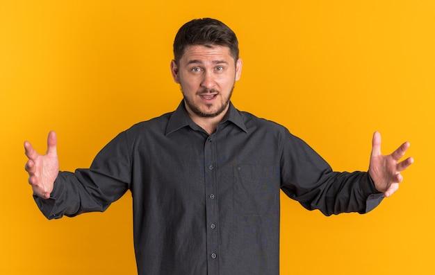 Pod wrażeniem młodego blondyna, przystojny mężczyzna robi ogromny znak patrząc na przód odizolowany na pomarańczowej ścianie