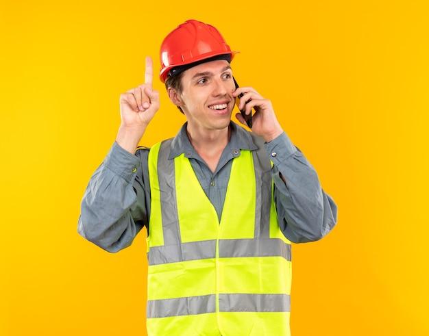 Pod wrażeniem młodego budowniczego mężczyzny w mundurze mówi przez punkty telefoniczne na górze izolowane na żółtej ścianie
