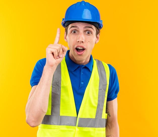 Pod wrażeniem młodego budowniczego mężczyzny w mundurze wskazuje na górę