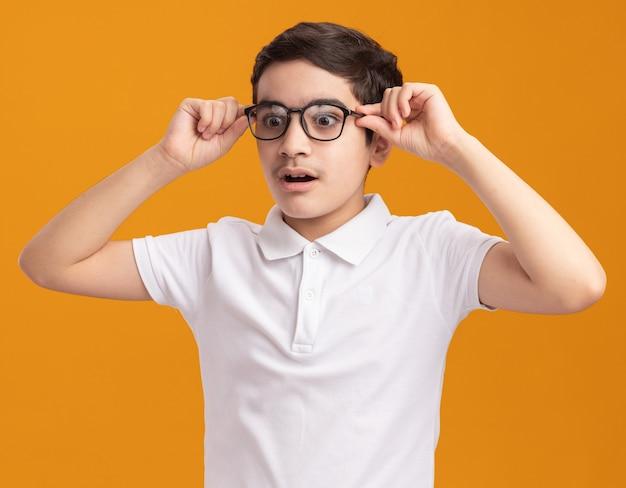 Pod wrażeniem młodego chłopca noszącego i chwytającego okulary patrzącego w dół izolowanego na pomarańczowej ścianie