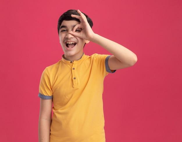 Pod wrażeniem młodego chłopca patrzącego z przodu, wykonującego gest spojrzenia na różowej ścianie z miejscem na kopię