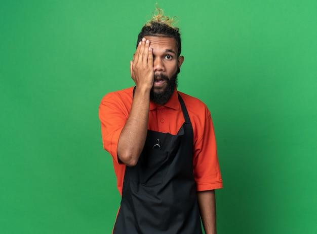 Pod wrażeniem młodego fryzjera męskiego noszącego mundur zakrywający połowę twarzy ręką patrzącą na przód na zielonej ścianie z miejscem na kopię