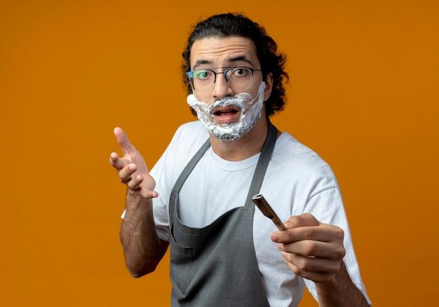 Pod wrażeniem młodego fryzjera płci męskiej rasy kaukaskiej w okularach i falistej opasce do włosów w mundurze, trzymającego brzytwę z kremem do golenia założonym na twarz, trzymającego brzytwę i trzymającego rękę w powietrzu