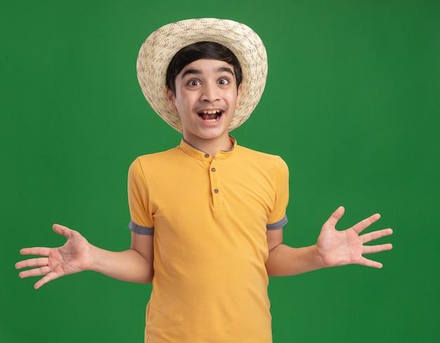 Pod wrażeniem młodego kaukaskiego chłopca w kapeluszu plażowym pokazującym puste ręce z otwartymi ustami