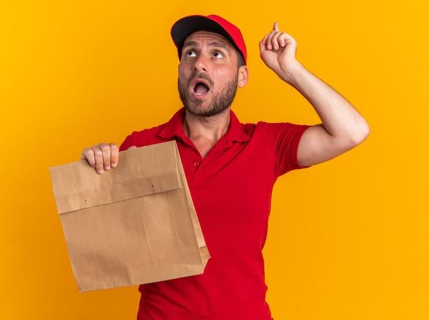 Pod wrażeniem młodego kaukaskiego dostawcy w czerwonym mundurze i czapce, trzymającego papierowy pakiet patrzący i wskazujący w górę na pomarańczowej ścianie