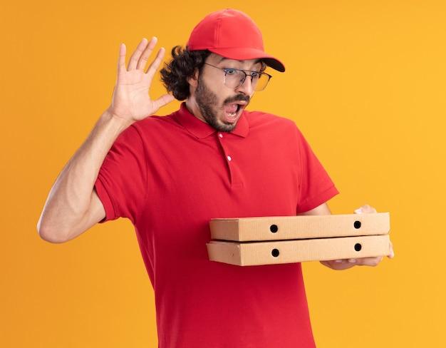 Pod wrażeniem młodego kaukaskiego dostawcy w czerwonym mundurze i czapce w okularach, trzymających i patrzących na paczki pizzy, podnoszące rękę w górę izolowane na pomarańczowej ścianie