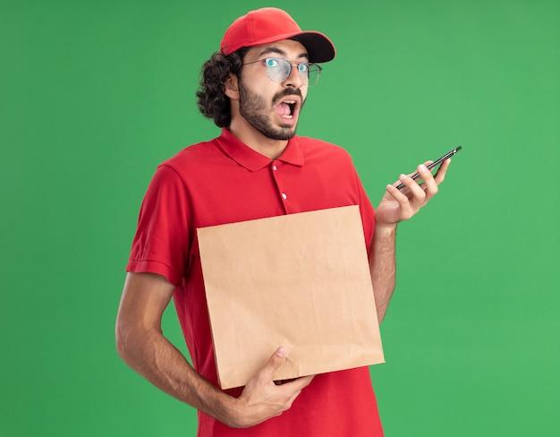 Pod wrażeniem młodego kaukaskiego dostawcy w czerwonym mundurze i czapce w okularach trzymających papierową paczkę i telefon komórkowy na zielonej ścianie