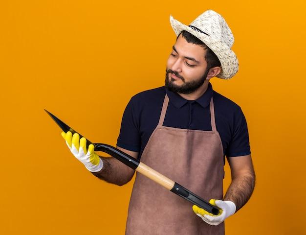 Pod wrażeniem młodego kaukaskiego ogrodnika płci męskiej w kapeluszu ogrodniczym i rękawiczkach, trzymającego i patrzącego na łopatę odizolowaną na pomarańczowej ścianie z kopią przestrzeni