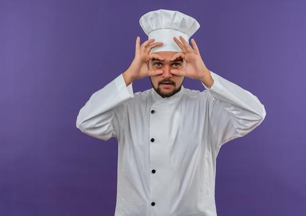 Pod wrażeniem młodego kucharza w mundurze szefa kuchni robi gest spojrzenia, używając rąk jako lornetki odizolowanej na fioletowej ścianie