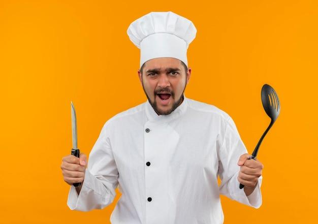 Pod wrażeniem młodego kucharza w mundurze szefa kuchni, trzymającego nóż i łyżkę cedzakową na pomarańczowej ścianie