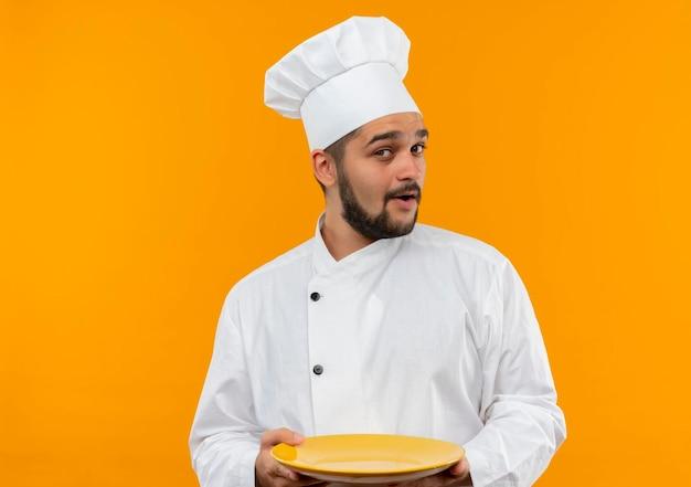 Pod wrażeniem młodego kucharza w mundurze szefa kuchni, trzymającego pusty talerz na pomarańczowej ścianie