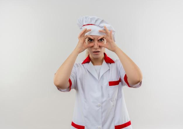 Pod wrażeniem młodego ładnego kucharza w mundurze szefa kuchni robi gest spojrzenia, używając rąk jako lornetki izolowanej na białej ścianie white