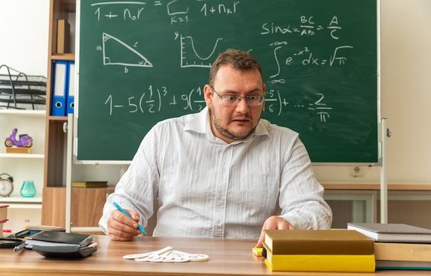 Pod wrażeniem młodego nauczyciela w okularach siedzącego przy biurku z przyborami szkolnymi w klasie, trzymającego długopis, dotykającego i patrzącego na papierowe notatki