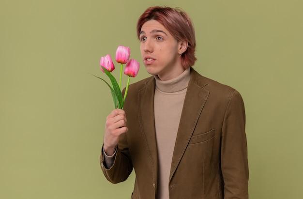 Pod wrażeniem młodego, przystojnego mężczyzny trzymającego kwiaty i patrzącego na bok