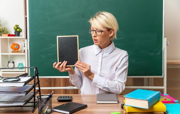 Pod wrażeniem młodej blond nauczycielki w okularach siedzącej przy biurku z przyborami szkolnymi w klasie pokazującej mini tablicę patrzącą na nią