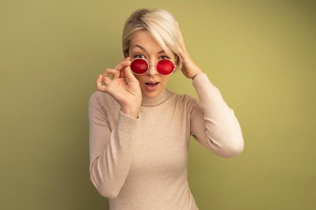 Pod wrażeniem młodej blondynki noszącej okulary przeciwsłoneczne i trzymającej okulary przeciwsłoneczne, która patrzy na głowę, odizolowaną na oliwkowozielonej ścianie z miejscem na kopię