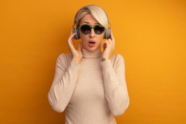 Pod wrażeniem młodej blondynki w okularach przeciwsłonecznych i słuchawkach dotykających słuchawek odizolowanych na pomarańczowej ścianie z miejscem na kopię