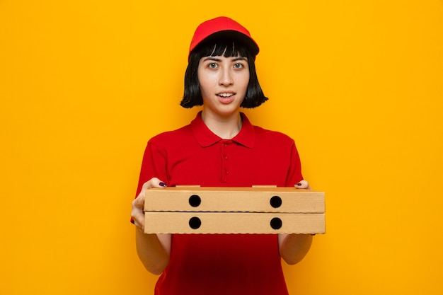 Pod wrażeniem młodej kaukaskiej dostawy kobiety trzymającej pudełka po pizzy