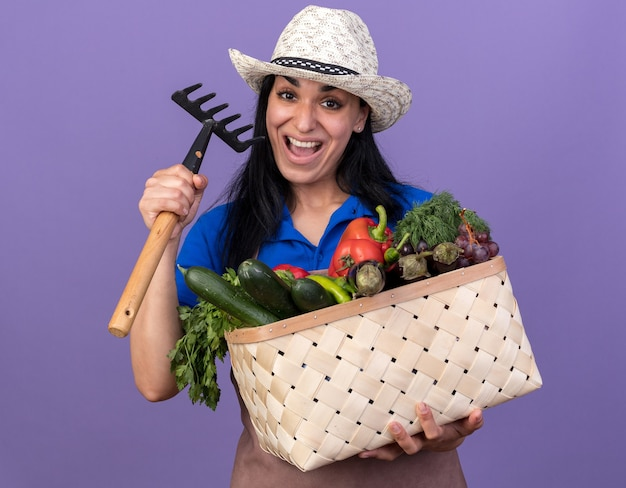 Pod wrażeniem młodej kaukaskiej ogrodniczki w mundurze i kapeluszu, trzymająca kosz warzyw i grabie