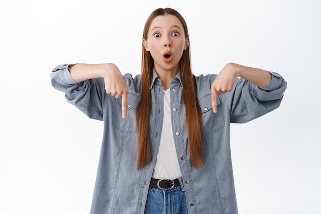 Pod wrażeniem młodej kobiety opadającej szczęki, wskazującej palcami na dole, tekst promocyjny reklamy poniżej, stojący nad białą ścianą
