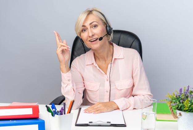 Pod wrażeniem młodej operatorki call center noszącej zestaw słuchawkowy siedzący przy stole z narzędziami biurowymi wskazującymi na górę na białym tle na białej ścianie