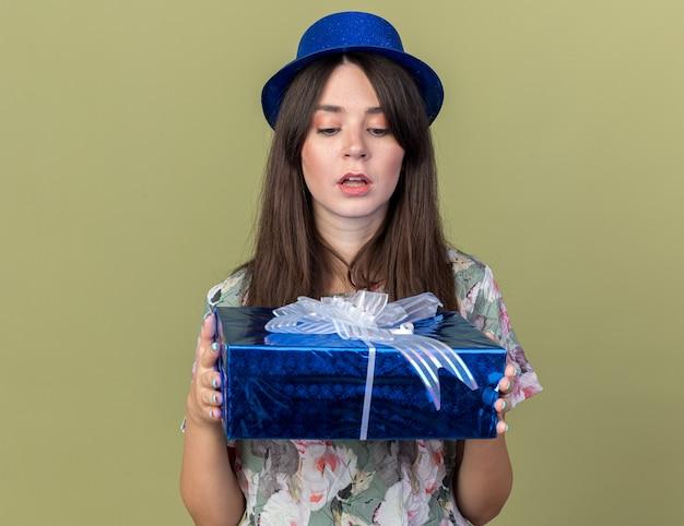 Pod wrażeniem młodej pięknej kobiety noszącej imprezowy kapelusz, trzymającej i patrzącej na pudełko na prezent na oliwkowozielonej ścianie