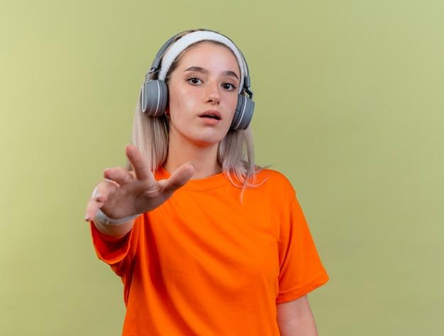 Pod wrażeniem młodej sportowej dziewczyny rasy kaukaskiej z szelkami na słuchawkach, noszącej opaskę na głowę i opaski na nadgarstkach wyciągające rękę