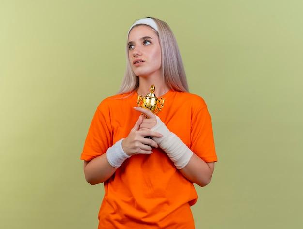 Pod wrażeniem młodej sportowej dziewczyny rasy kaukaskiej z szelkami w opasce i opaskach na nadgarstkach trzyma puchar zwycięzcy patrząc na bok