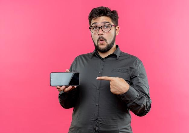 Pod wrażeniem młody biznesmen w okularach trzyma i wskazuje na telefon na białym tle na różowej ścianie