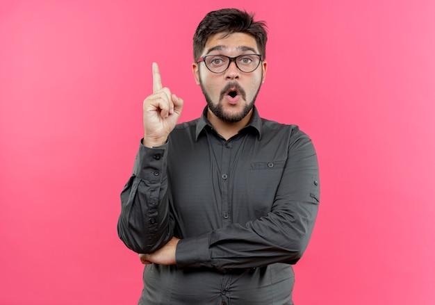 Pod wrażeniem młody biznesmen w okularach wskazuje na górę na białym tle na różowej ścianie