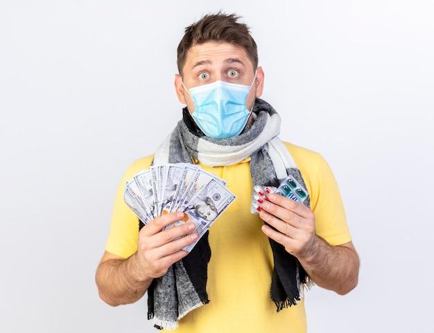 Pod wrażeniem młody blondyn chory ubrany w maskę medyczną i szalik trzyma pieniądze i paczki pigułek medycznych na białej ścianie