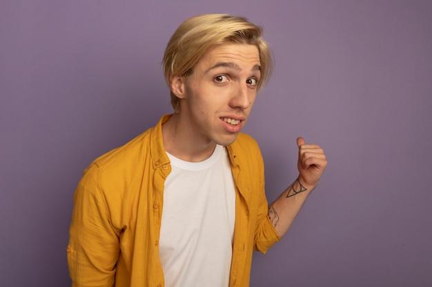Pod wrażeniem młody blondyn ubrany w żółtą koszulkę wskazuje na tył na białym tle na fioletowo z miejsca na kopię